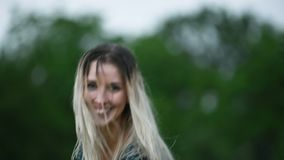 Close-up portrait of a happy attractive Caucasian blonde girl with wet hair during a rain on the nature outdoor on a stock video
