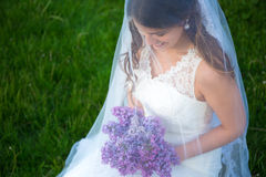 Close up portrait of happy beautiful bride with lilac flowers Royalty Free Stock Images