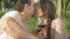 Happy beautiful couple drinking wine and kissing
