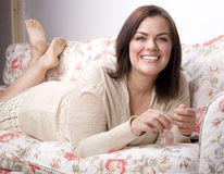 Close up portrait of happy beautiful girl on sofa color her nails Royalty Free Stock Image