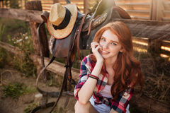 Close up portrait of a happy beautiful redhead cowgirl resting. At the ranch fence stock photos