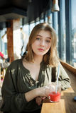 Close up portrait of happy beautiful teen student girl with a glass mug straw fruit tea at street cafe sitting near big window Stock Images