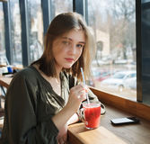 Close up portrait of happy beautiful teen student girl with a glass mug straw fruit tea at street cafe sitting near big window Stock Photos
