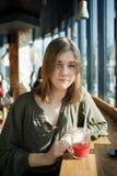 Close up portrait of happy beautiful teen student girl with a glass mug straw fruit tea at street cafe sitting near big window bit Stock Image