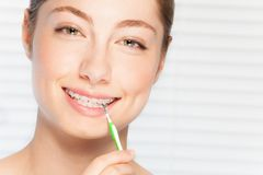 Woman cleaning teeth brace by interdental brush. Close-up portrait of happy beautiful young woman cleaning her teeth brace by interdental brush Stock Image