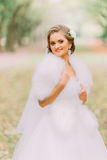 Close-up portrait of happy blonde bride in white dress and fur boa on lane at the autumn park. Portrait of happy blonde bride in white dress and fur boa on the Stock Images