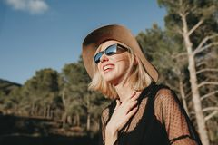 Cool young girl laughing outdoors in nature. Close up portrait of happy blonde woman with hat and sunglasses laughing in nature with sunlight in her face Stock Photo