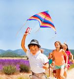 Happy boy flying rainbow kite with his friends stock images