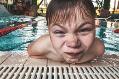 Close-up portrait of happy boy in the swimming pool at aquapark. Cute child having fun enjoyable time on vacation. Looking at cam stock photos