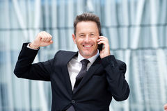 Close up happy business man on talking on phone with hand raised Stock Images