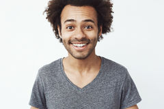 Close up portrait of happy and charming african guy smiling at camera, a boyfriend waiting for a date, or a head hunter Royalty Free Stock Photo