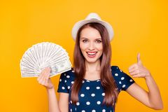 Close up portrait of happy cheerful attractive lucky girl holdin. G money fan in hands near face, having white hat on head, gesture thumb up simbol, isolated on Royalty Free Stock Images