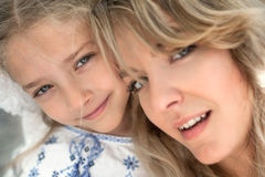 Close-up portrait of happy cheerful beautiful young mother with her little smiling daughter. Royalty Free Stock Images