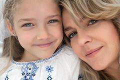 Close-up portrait of happy cheerful beautiful young mother with her little smiling daughter. Stock Photos