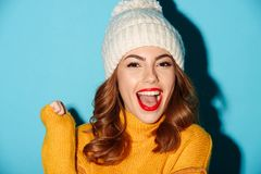 Close up portrait of happy cheerful girl in winter hat. Looking at camera with mouth open isolated over blue background Stock Photography