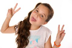 Close-up portrait of happy child girl makes comical face and shows her tongue. Close-up portrait of happy pretty cheerful teenage girl. The child funny poses Stock Photos