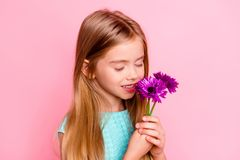 Close up portrait of happy cute lovely beautiful tender gentle g. Irl with toothy smile, she is smelling flowers in hands with closed eyes, isolated on bright Royalty Free Stock Photo