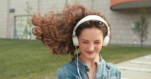Close-up portrait of the happy emotional girl with curly dark hair and braces listening to music via white headphones stock video footage