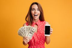 Close-up portrait of happy exited young brunette woman holding f. An of money, showing blank mobile screen, looking at camera, isolated on yellow background Royalty Free Stock Photography