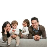 Portrait of happy family laying on couch. Stock Photography