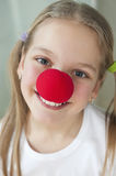 Close-up portrait of a happy girl with red clown nose Royalty Free Stock Image