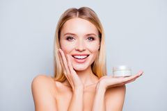 Close up portrait of happy gorgeous smiling attractive satisfied. Young woman with beaming smile, she is holding a cream jar and touching her cheek, isolated on Stock Photography