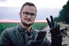 Close up portrait of a happy handsome young man in glasses and leather jacket and gloves, uses a smartphone, like this moment a stock photos