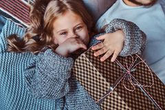 Close-up portrait of a happy little girl in warm sweater holds gifts while lying on bed. royalty free stock photo