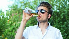 Close-up portrait of happy man in sunglasses drinks a beer while resting in park on sunset stock video