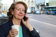 Close up portrait of happy mature Caucasian woman talking on cellphone in the city Royalty Free Stock Photography