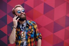 Close up portrait of happy mature guy talking on cell phone and smiling, isolated on a colorful background. stock photos