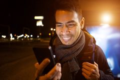 Happy asian man smiling with a phone at night. Close up portrait of happy middle aged asian man looking at his mobile phone and smiling outdoors in city at night Royalty Free Stock Image