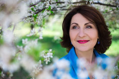 Close up portrait of happy middle aged woman in blooming garden. Close up portrait of happy middle aged woman in blooming summer garden royalty free stock image