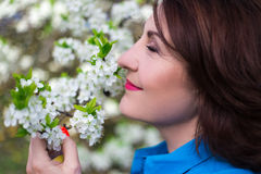 Close up portrait of happy middle aged woman smelling cherry tre Stock Photo