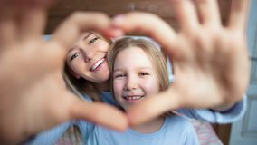 Close-up portrait of happy mother and daughter showing gesture love heart by hands