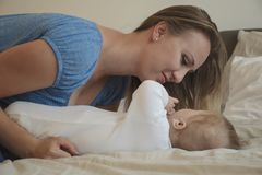 Close-up portrait of mother with her baby on bed in bedroom. Young attractive mom loves her son. Happy family. Mother's day stock photography