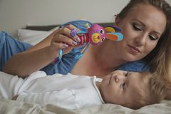 Close-up portrait of happy mother with her baby on bed in bedroom. Young blonde mom playing with her son. Baby looking at the toy stock photography