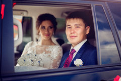 Close up portrait of happy newlyweds in a car window Royalty Free Stock Images