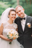 The close-up portrait of the happy newlyweds having fun in the park. stock photos