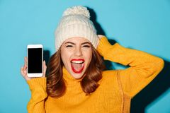 Close up portrait of a happy pretty girl. Dressed in winter clothes showing blank screen mobile phone and screaming isolated over blue background Royalty Free Stock Photo
