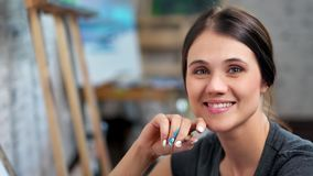 Close-up portrait of happy pretty young female painter relaxing at art studio looking at camera. Face of charming smiling artist woman holding gray pencil stock footage