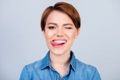 Close up portrait of happy pretty young girl with short hair and. Jeans shirt licking lips and giving a wink Royalty Free Stock Photo