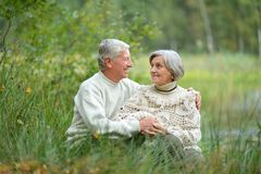 Close-up portrait of happy senior couple sitting by pond royalty free stock images