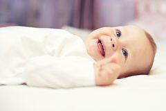 Close-up portrait of happy smiling baby in bed Stock Image