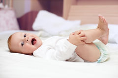 Close-up portrait of happy smiling baby in bed. Close-up portrait of happy smiling beautiful baby lying on bed Royalty Free Stock Photography