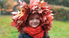 Close-up portrait of happy smiling beautiful cute little girl in a wreath crown of autumn maple leaves slow motion. Close-up portrait of happy smiling beautiful stock video