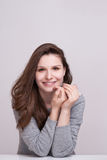 Close up portrait of a happy smiling woman resting her chin on her hands and looking directly at the camera Royalty Free Stock Photography