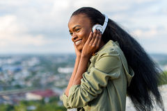 Close-up portrait of happy smiling young black african american woman listening to music. Blurred cityscape on Royalty Free Stock Photos