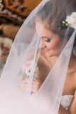 Close up portrait of happy stylish blonde bride in luxury white dress with bouquet under the veil Royalty Free Stock Image