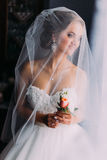 Close up portrait of happy stylish blonde bride in luxury white dress with bouquet under the veil Stock Photography